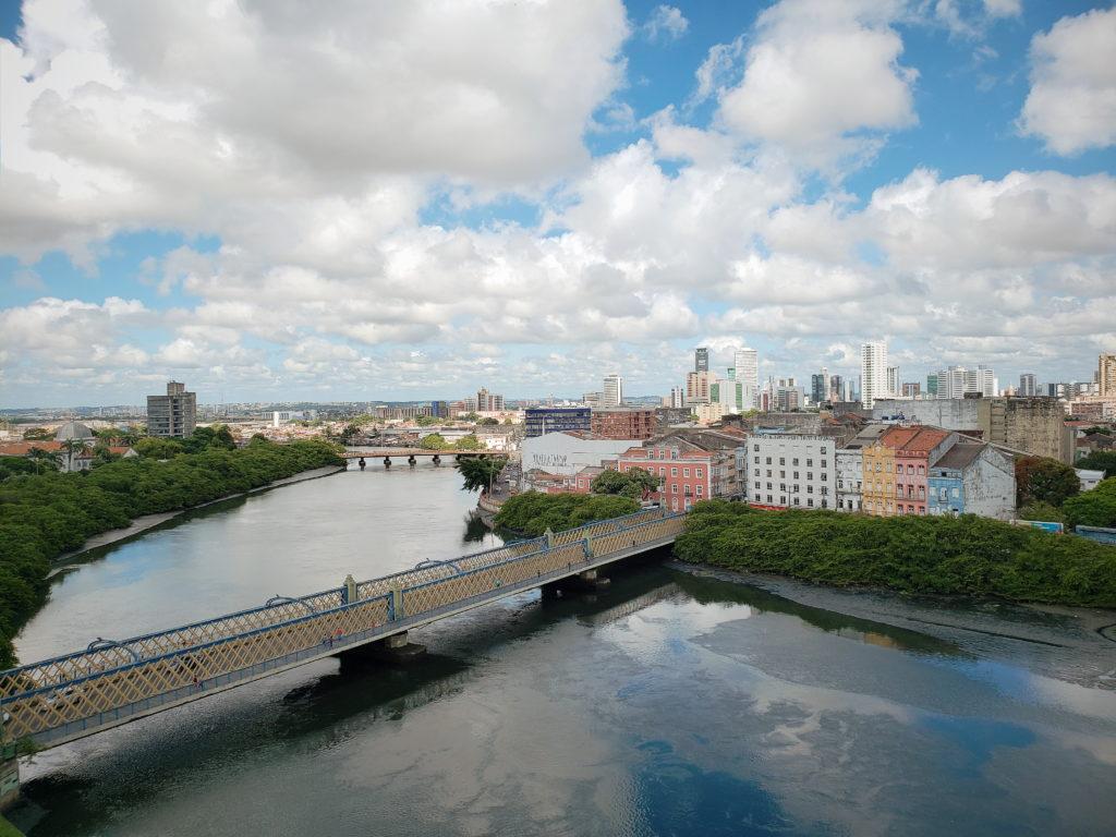 Imagem da Ponte Velha, no Recife, com o Rio Capibaribe abaixo e casarios coloridos ao fundo, do lado direito.