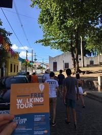 Imagem de panfleto do free walking tour de Olinda, com casario da cidade ao fundo.